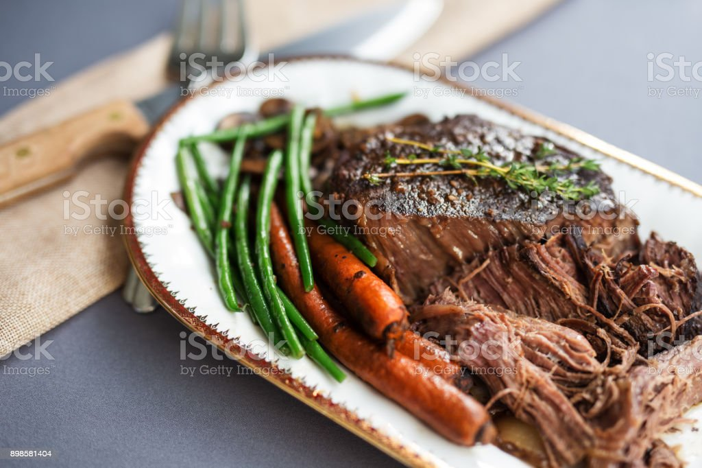 Slow cooked pot roast served with organic carrots, fresh green beans and sliced white mushrooms. Thyme garnish. stock photo