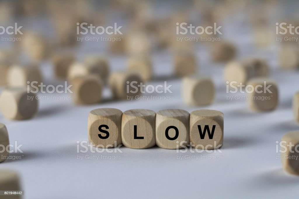 slow - cube with letters, sign with wooden cubes stock photo
