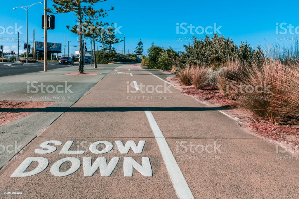 Slow Down sign written on shared footpath for cyclists and pedestrians stock photo