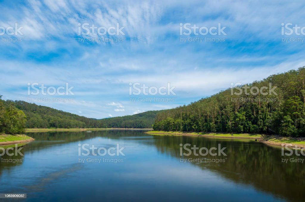Slow flowing river meanders through riverbanks stock photo