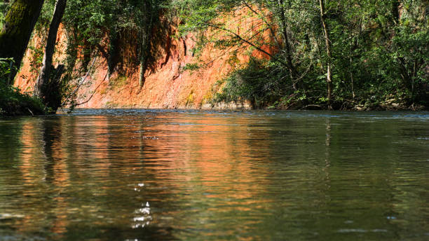 Slow flowing river with an ochre colored bank stock photo