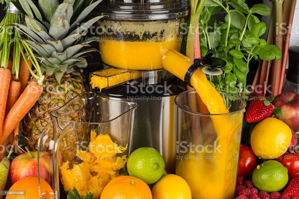 slow juicer in kitchen with many fruit and vegetable orange vitamin...