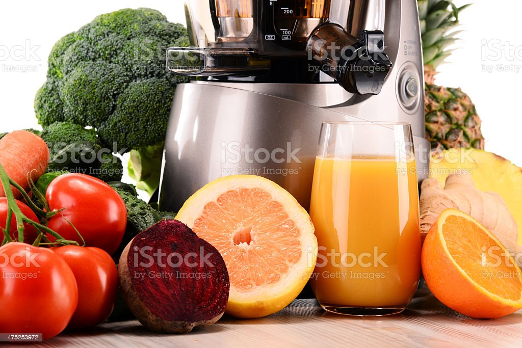 Slow juicer with organic fruits and vegetables isolated on white stock photo