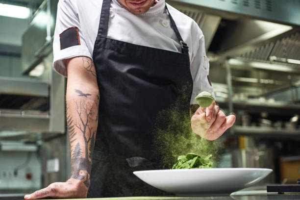 Slow motion. Cropped image of chef's hands with tattoos adding spices in salad while standing in a restaurant kitchen. Slow motion. Cropped image of chef's hands with tattoos adding spices in salad while standing in a restaurant kitchen. Food concept. Food conept. chef stock pictures, royalty-free photos & images