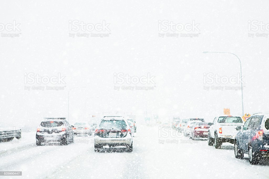 Slow moving freeway traffic during a winter snow storm blizzard stock photo