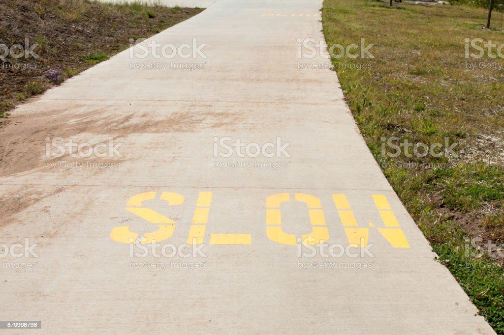 Slow painted on a concrete path through a park stock photo
