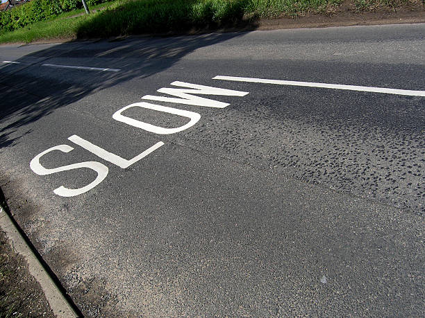 Slow! Slow lettering on an English road. skeable stock pictures, royalty-free photos & images