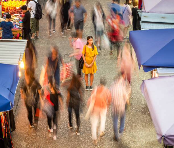 Slowing down A woman stationary among the people moving around her, at a night market in Hong Kong. asian market stock pictures, royalty-free photos & images