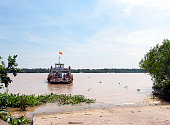 Sun Phu Ferry, Mekong Delta, South Vietnam. Water craft traffic such as barges, houseboats, passenger craft, industrial freighters and small personal boats travel the green rippled waters of the channels and routes of the mighty Mekong River as it flows to the Mekong Delta, South Vietnam