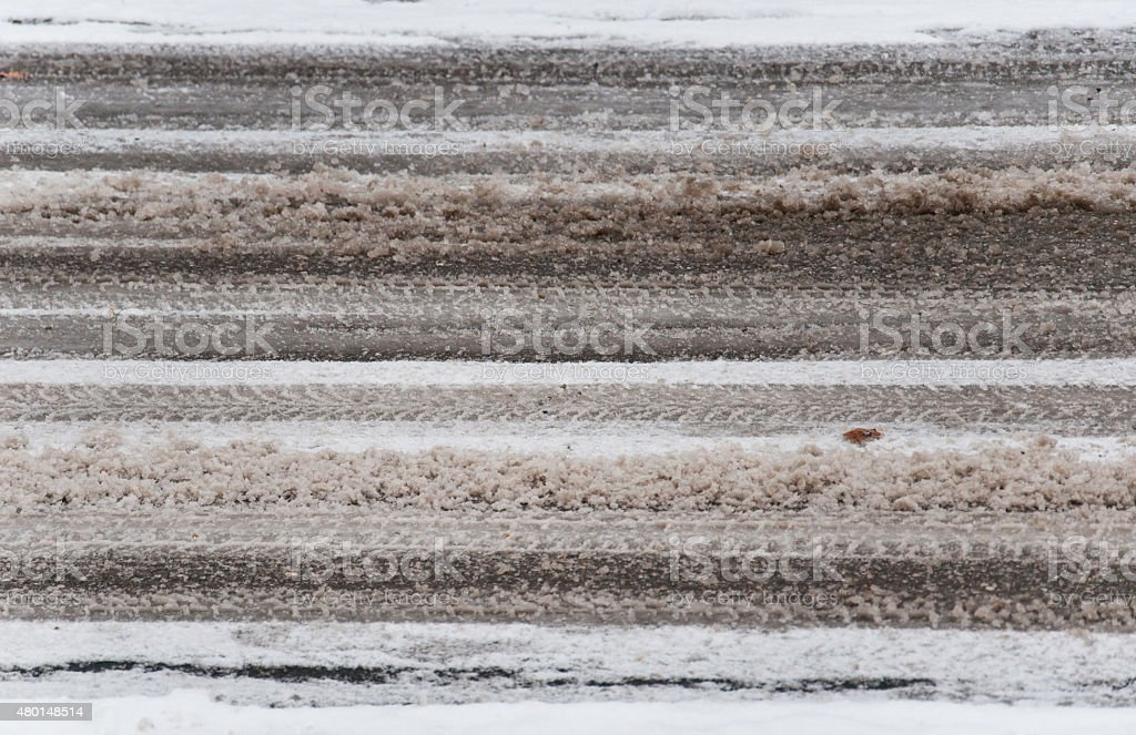 sludgy snow texture with skid marks on the street stock photo