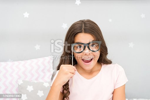 Slumber party photo booth props. Kid girl cheerful posing with vintage black eyeglasses party attribute. Prepare photo booth props hand made or buy for party. Printable photo booth props pajama party.