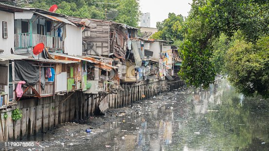 Slums along a smelly polluted canal (Khlong Toei) full of mud and garbage in Khlong Toei District. Stock image with logos removed.