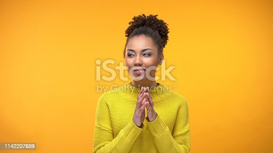 istock Sly Afro-American female thinking of idea on yellow background, tricky plan 1142207659