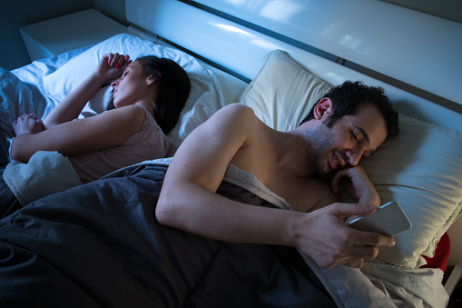 istock Sly boyfriend using mobile in bed 541131642