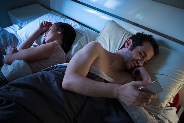 Sly boyfriend using mobile in bed stock photo