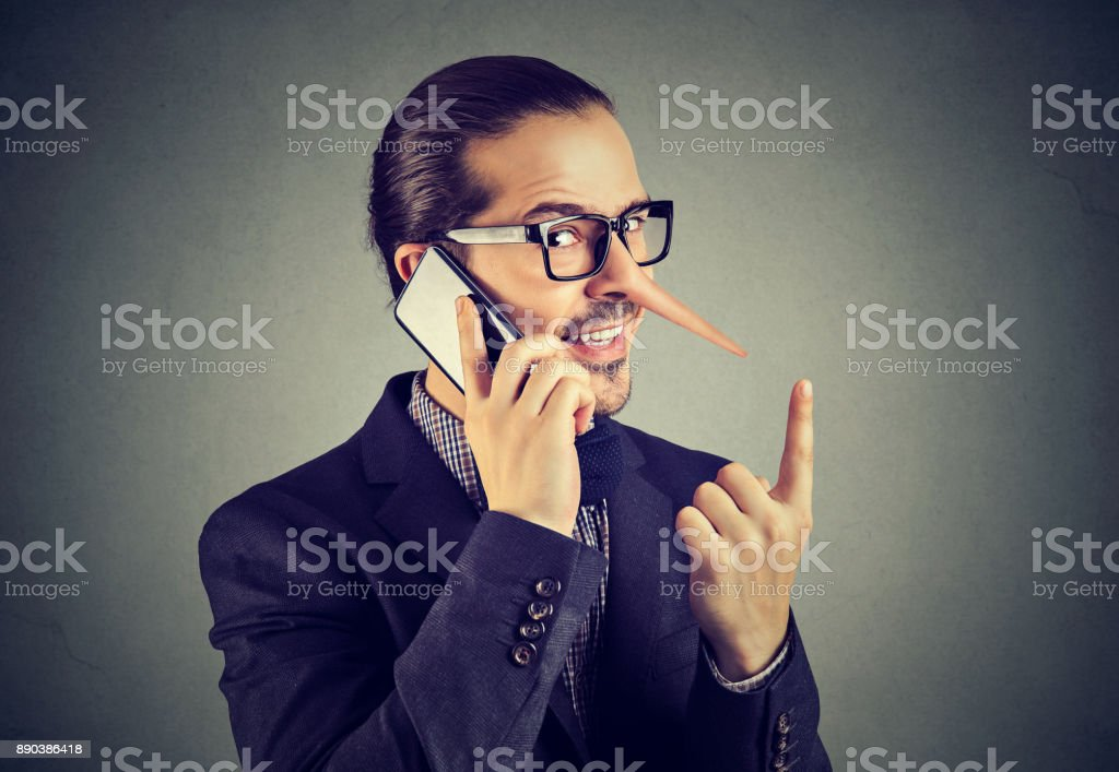 Sly liar business man with long nose talking on mobile phone isolated on gray wall background. stock photo