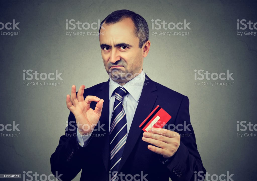 Sly liar businessman employee reassuring their credit card is the best stock photo