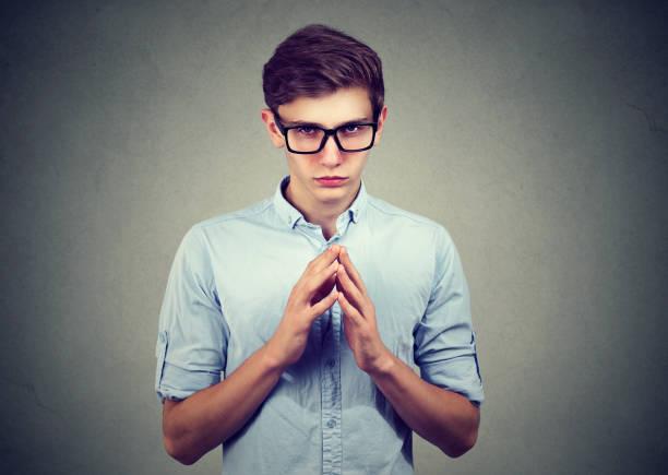 Homem astuto, calculista, tentando traçar algo ferrar alguém isolado em fundo cinza. - foto de acervo