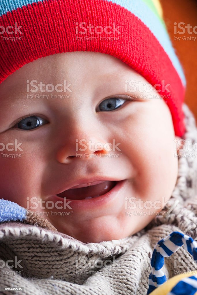 Smailing happy 8 months old boy with red beannie stock photo
