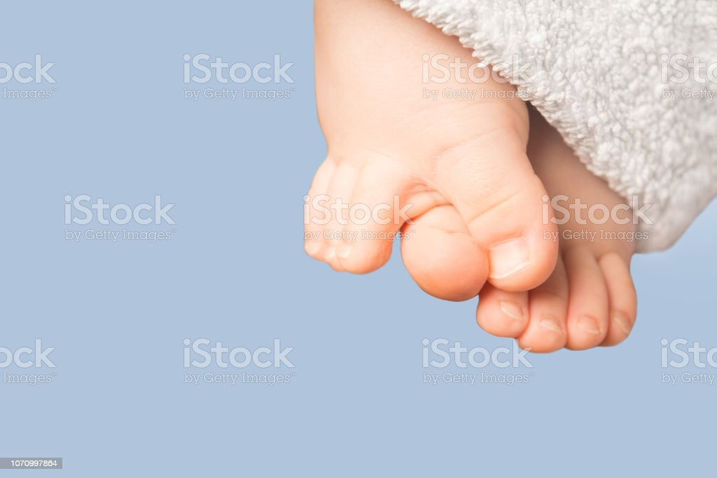 Smal baby feet with blue terry towel on blue background stock photo
