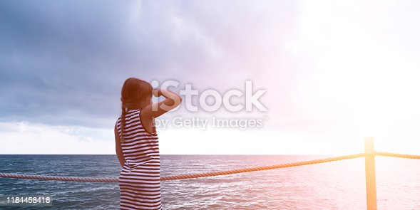 Beautiful little teenager girl standing on ship looking forward with hand near her face at seaside. Beautiful ocean morning landscape. Oriental calm, relax and harmony banner concept with copyspace
