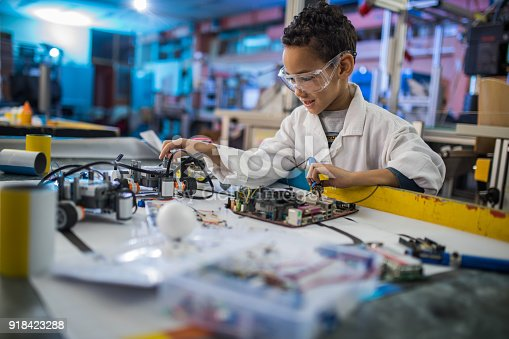 Little African American lab worker working on a computer motherboard in a laboratory while making futuristic robot.