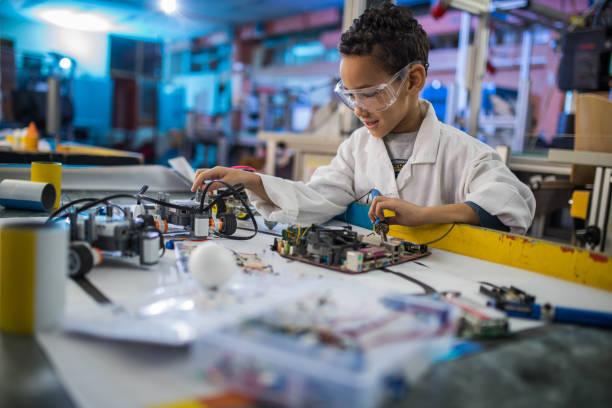 研究室でのコンピューターのマザーボードの修理小さなアフリカ系アメリカ人の電気技師。 ストックフォト