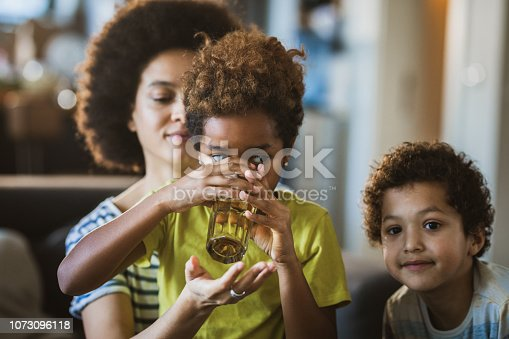 Black mother spending time with her kids at home while assisting her daughter in drinking water. Focus is on girl.