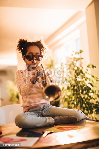 African American little girl sitting on the table while playing trumpet and having fun at home.