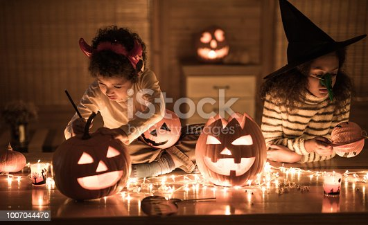 Two black siblings decorating Jack O' Lanterns on Halloween at home.