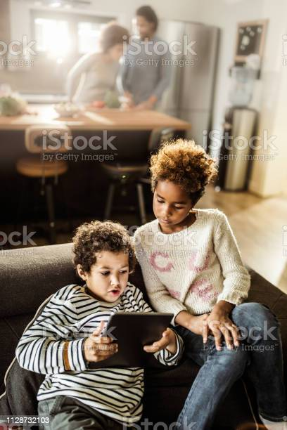 Small african american siblings using touchpad on sofa at home picture id1128732103?b=1&k=6&m=1128732103&s=612x612&h=xxcpfzdkrgumicuvfyosjb5xa9isf pbdckgcfwqz c=