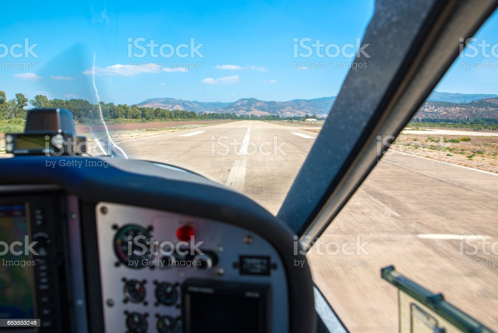Small aircraft landing at a local airport. Blurry and out of focus cockpit, selective focus on the runway and the scenery . stock photo