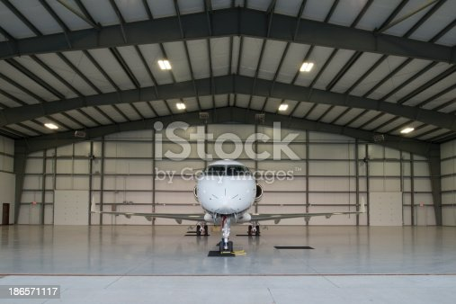 Head on perspective of a new mid-sized business jet poised for a mission in it's hangar.