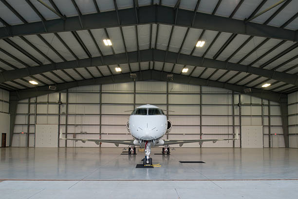 Small airline in a large garage setting  Head on perspective of a new mid-sized business jet poised for a mission in it's hangar. airplane hangar stock pictures, royalty-free photos & images