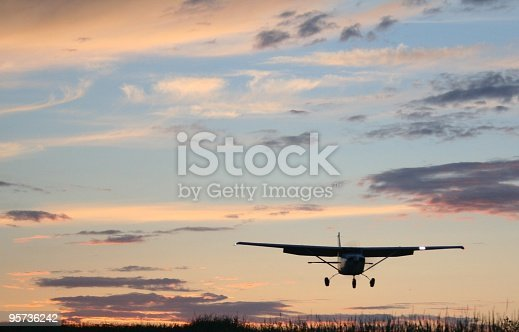 A single engine aircraft flying close to the ground near sunset.