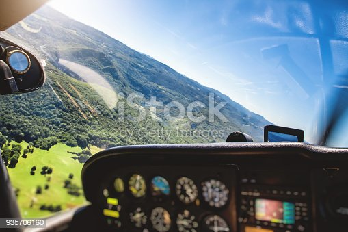 Vibrant color photography of small tourism airplane cockpit interior in selective soft focus with basic common and pretty old control instrument panel. Image taken flying without people, in middle of Ain nature, in Bugey mountains, in Auvergne-Rhone-Alpes region in France (Europe), with hilly lush foliage landscape background in summer season.