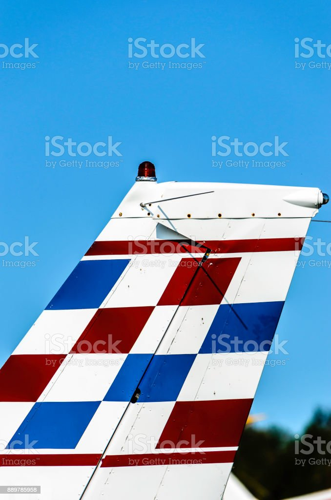Small airplane red, white & blue tail fin against a blue sky