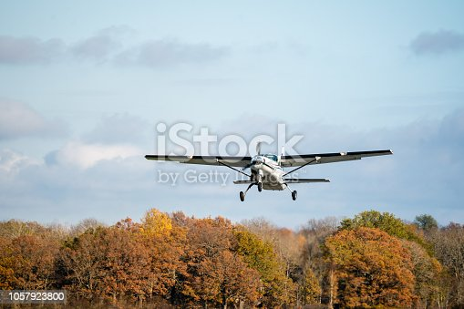 Small plane with single propeller taking of from the runway. Sunshine and autumn colored trees in the background
