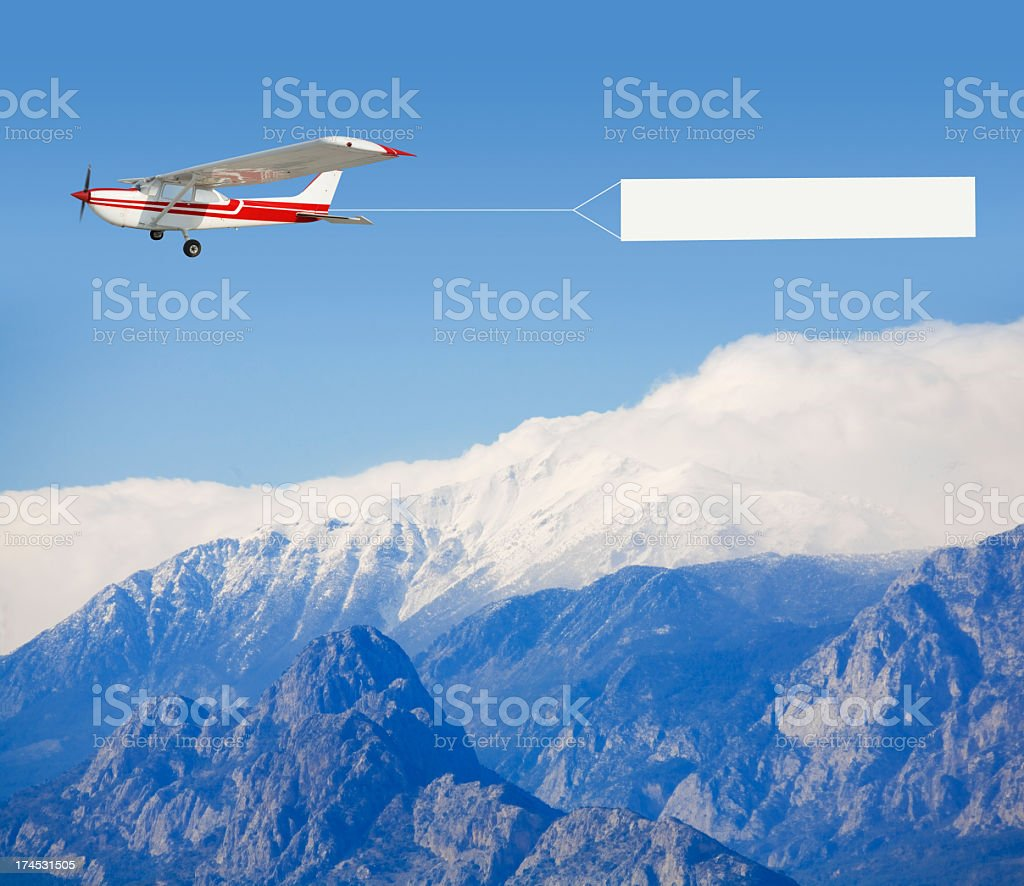A small airplane towing a banner over a mountain landscape royalty-free stock photo