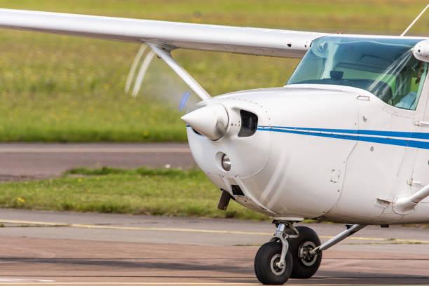 kleines flugzeug während der fahrt am flughafen mit drehendem propeller - flugschule stock-fotos und bilder