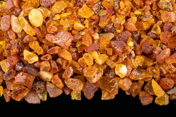 Small amber stones on a dark table. A pile of small ambers found on the Baltic beach. Black background. Small amber stones on a dark table. A pile of small ambers found on the Baltic beach. Black background. fossilized pitch stock pictures, royalty-free photos & images