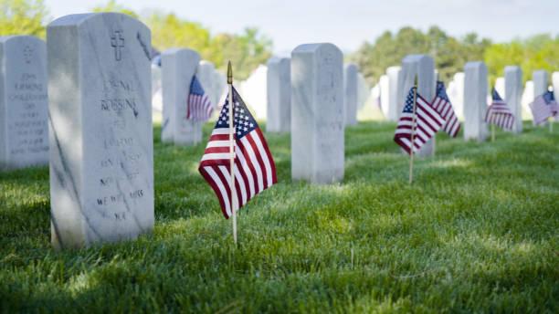 pequeñas banderas americanas junto a lápidas de mármol blanco - memorial day fotografías e imágenes de stock