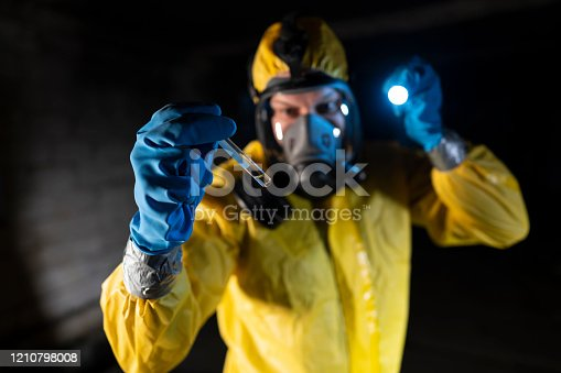 Man in protective workwear holding a test tube with toxic substance.