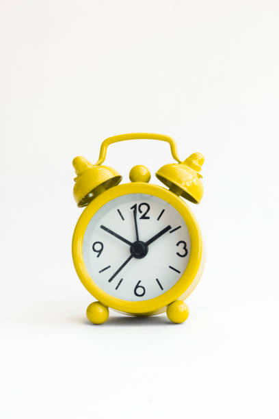 small analogue yellow golden clock in isolated white background stock photo