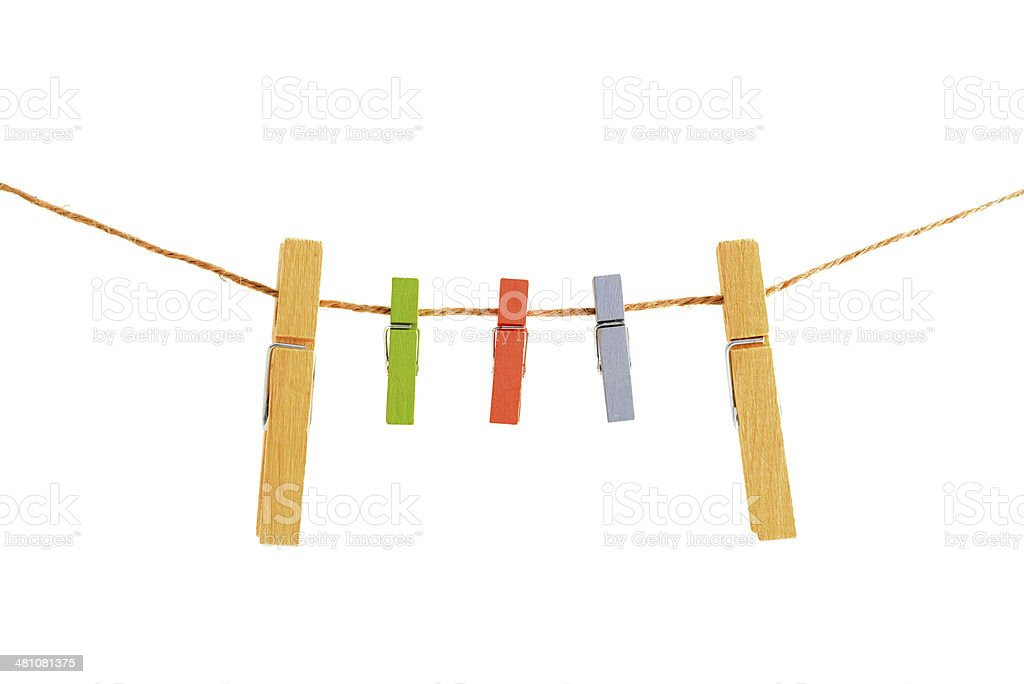 Small and large clothepins on clothesline with white background stock photo