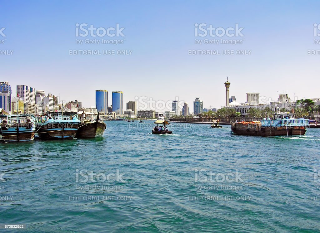 Small and large ships sail on the Dubai Creek in the UAE stock photo