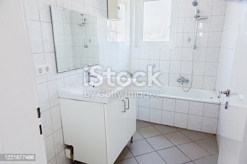 simple bathroom with sink, mirror and bathtub in a small room with white tiles at the wall