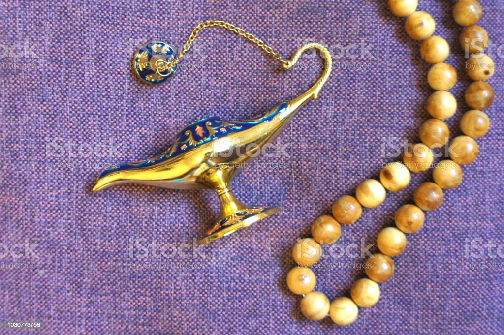 Small Antique magic Aladdin Lamp and rosary. Top view. стоковое фото