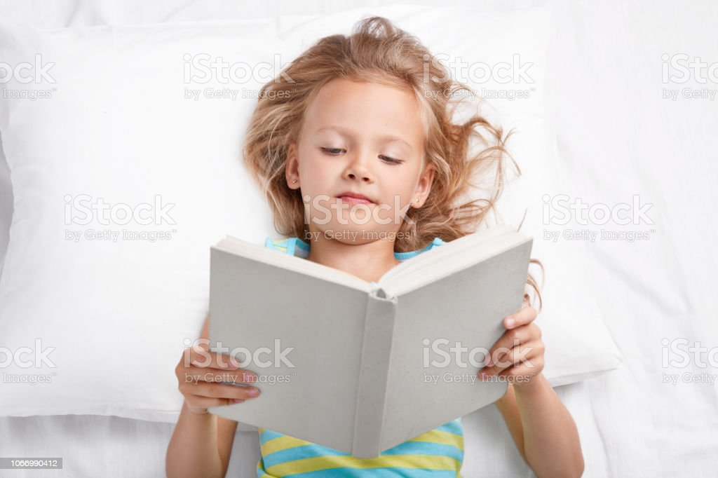 Small appealing female kid rests in bed with book, reads interesting...