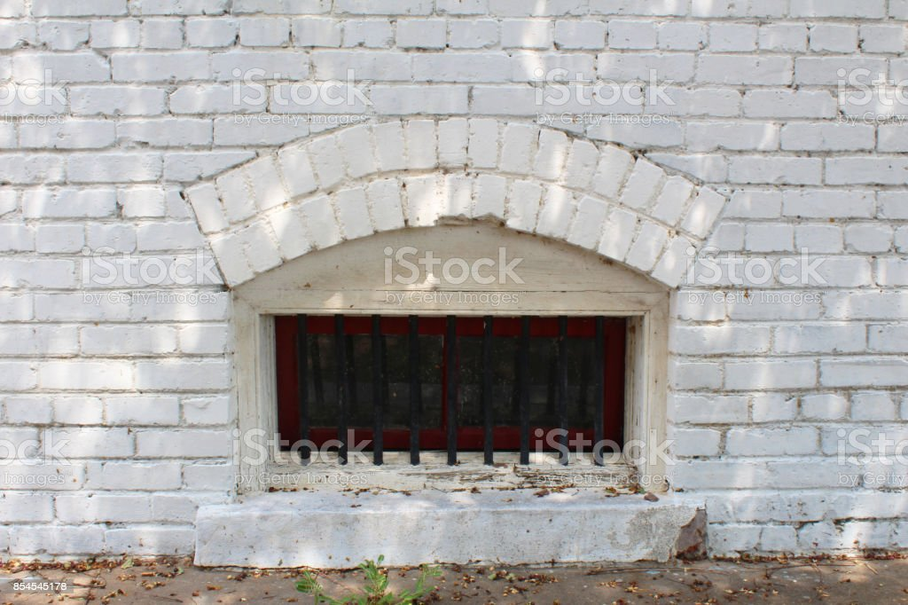 Small arched basement window with bars in a white brick wall,...